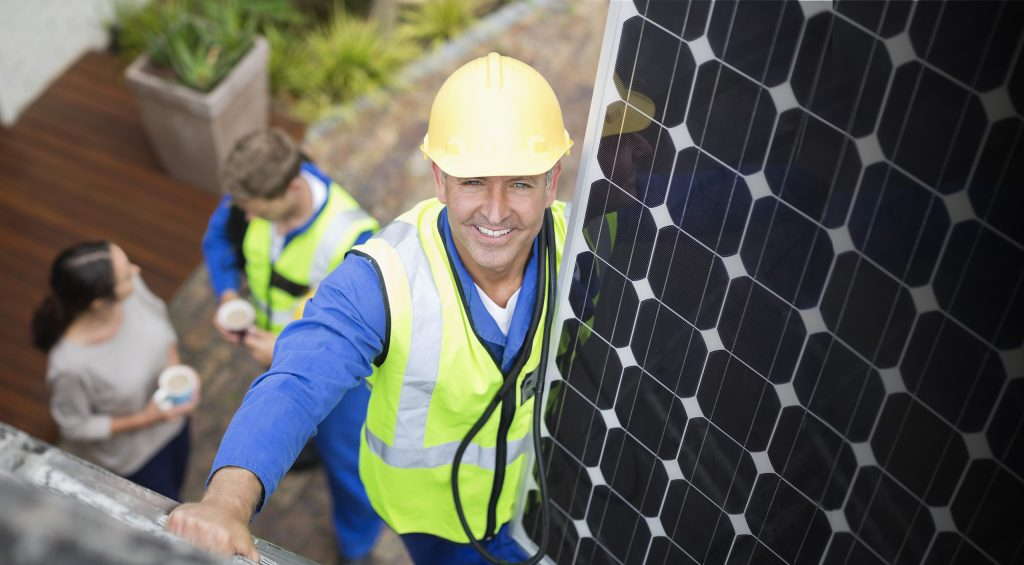 A solar panel installer is smiling at you.